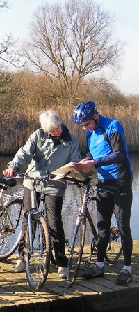 two cyclists consulting map blue top grey top