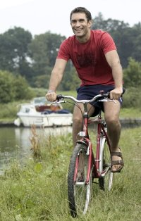 gent cycling red tee boat in background