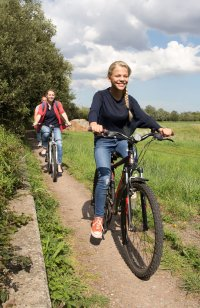 girl in jeans cycling with parents